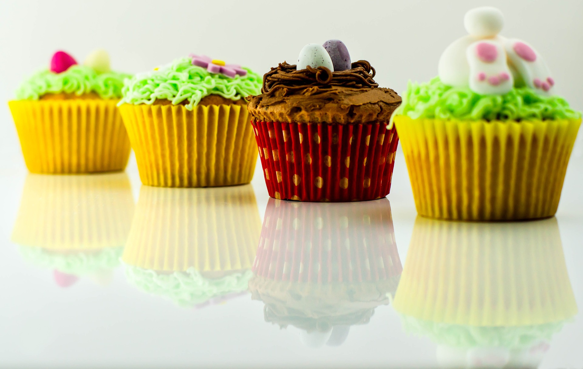 Four beautifully decorated cupcakes in colourful cases