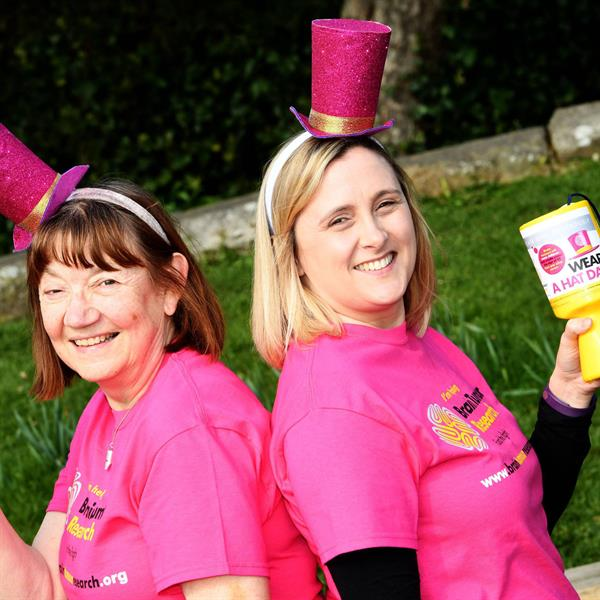 Wear A Hat Day - Two ladies wearing pink hats standing holding collection tins