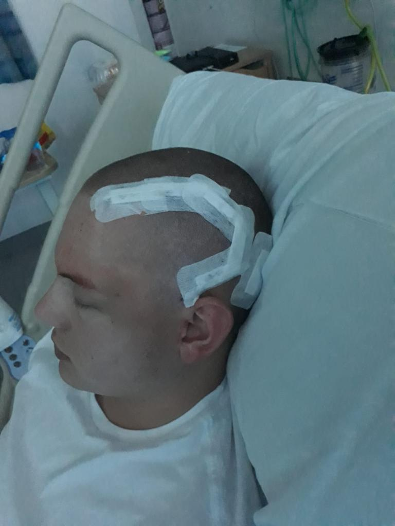 Man in hospital bed with bandage over scar