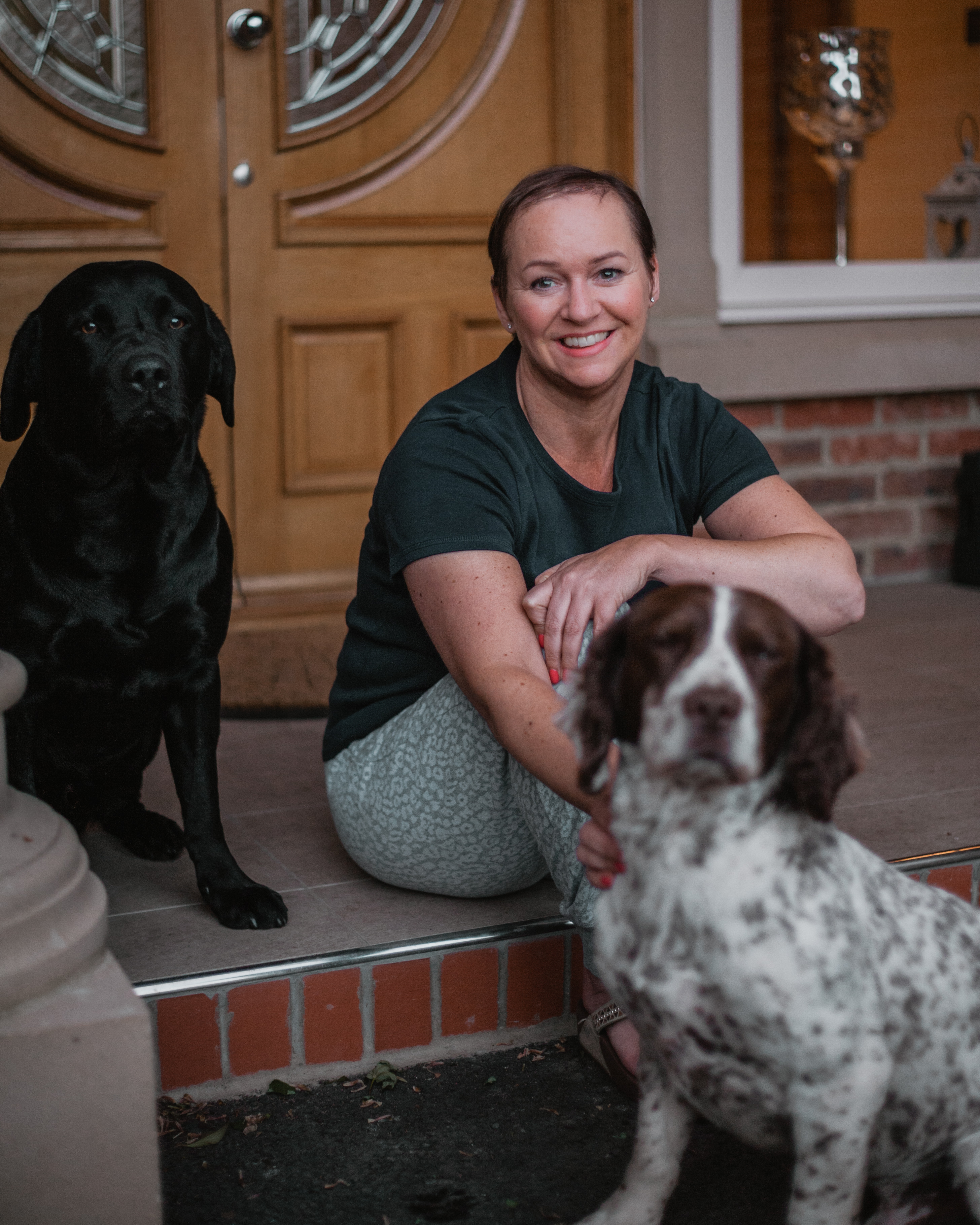 a woman sitting on stairs with dogs